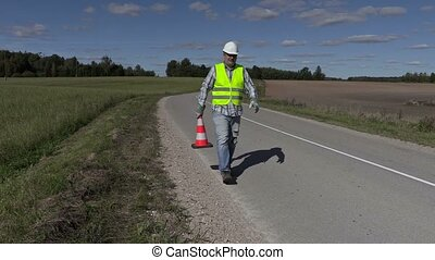 Road construction worker with traffic cone ask where put...