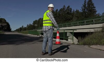 Road construction worker put traffic cone on highway and...