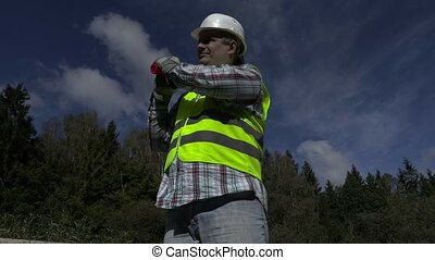 Road construction worker with traffic cone on shoulder