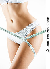 Blue measure on woman body on white background. Fashion photo of sexy young woman in lingerie with slim body sitting on a diet and measuring the waist with a centimeter tape