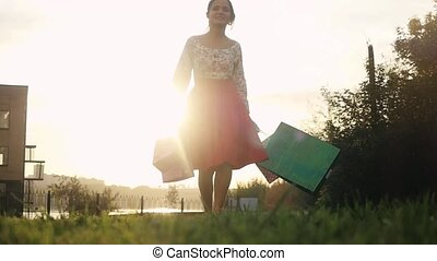 Shopaholic joyful woman in beautiful dress holding many...