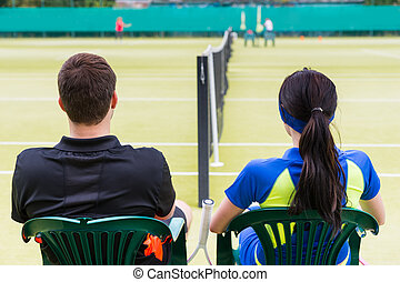 View from the back on a couple of tennis players having a rest on the chairs at the tennis court
