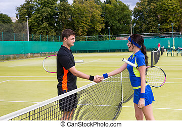 Two young tennis players shaking hands over the net