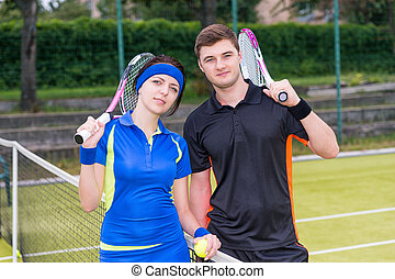Athletic couple of  tennis players holding a racket and a ball on tennis court at early morning