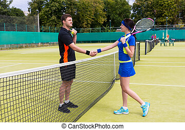 Couple of a tennis players shaking hands over the net