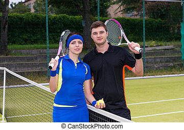 Young attractive couple of  tennis players holding a racket and a ball on tennis court at early morning