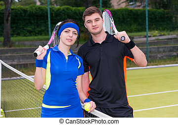 Young couple of  tennis players holding a racket and a ball on tennis court at early morning