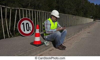 Road construction worker sitting and using tablet PC