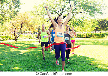 happy young female runner winning on race finish - fitness,...