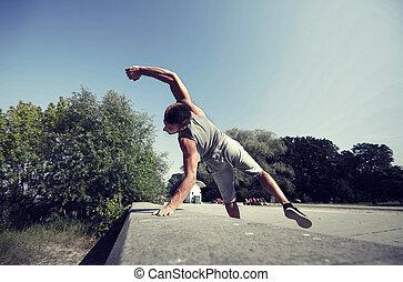 sporty young man jumping in summer park - fitness, sport,...