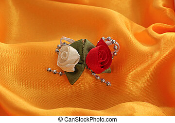 white and red fabric roses on satin like textile background
