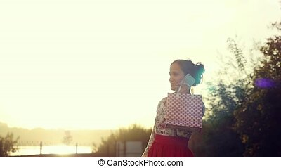 Beautiful young smiling woman with shopping colorful bags using and talk on the smartphone outdoors during sunset in slowmotion.