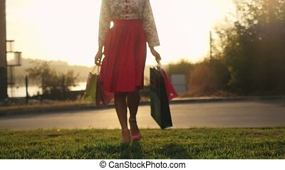 Blurred shopaholic woman in beautiful dress holding many...