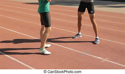 Two athlets warm up at the stadium - Two caucasian male...