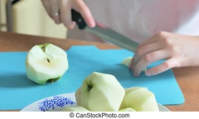 Young woman cutting an apple kitchen - Slicing apple Cutting...