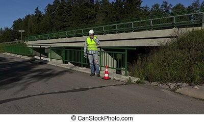 Road construction worker talking on phone on bridge near...