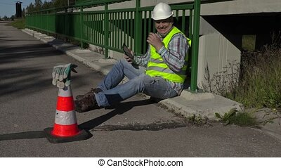 Road construction worker using tablet PC and laughing