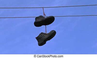 Old boots hanging on an electric wire on blue sky