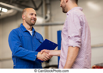 auto mechanic and man shaking hands at car shop - auto...