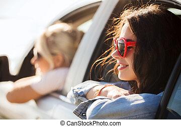 happy teenage girls or women in car at seaside - summer...