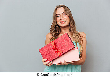 Cheerful attractive young woman standing and opening present...
