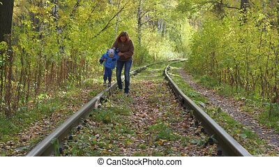 woman with child walking on railway road