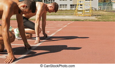 Two athlets starts to sprint at the stadium - Two young...