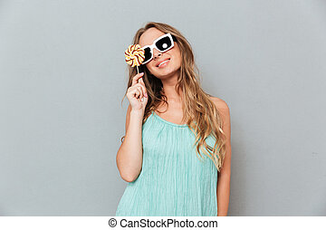 Happy young woman in sunglasses holding lollipop