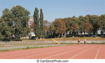 Two athlets run at the stadium - Two male athlets running by...