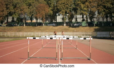 Two athlets run on short distance with hurdles at the...