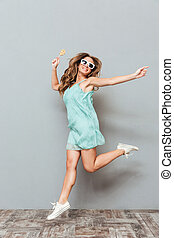 Full length of cheerful beautiful young woman in sunglasses...