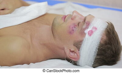 man with head injuries lying on the bed. bandaged head....