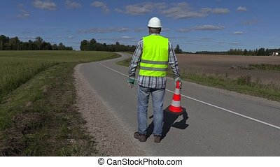 Road construction worker with traffic cone on the road