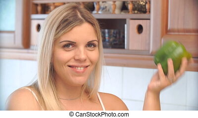 blonde woman holding a pepper in the kitchen