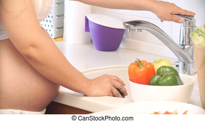 pregnant woman washing peppers in the kitchen. vegetables...