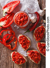 Ajvar in a glass jar and toast on a wooden background....