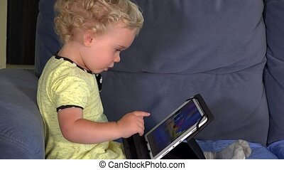 Emotional little girl playing game with tablet computer...