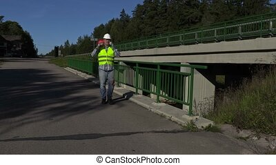 Road construction worker with traffic cone on shoulder...