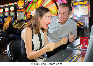 Man and woman winning casino slot machine
