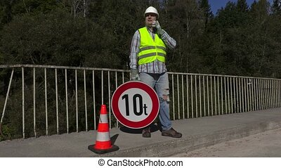 Road construction worker with limit road sign