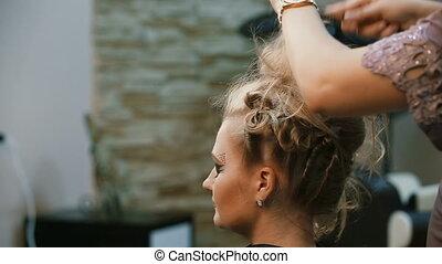 Hairdresser makes hairstyle girl. - Hairdresser makes...