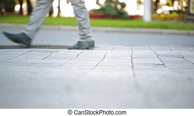 foot crosswalk. People cross the road. feet walking on the...