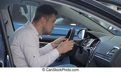 Man examines car interior at the dealership - Young man...