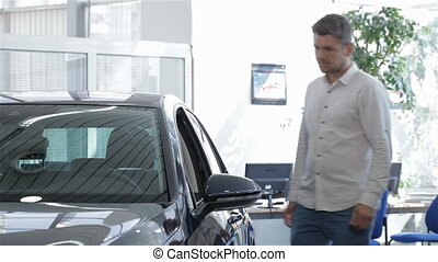 Man opens car door at the dealership - Attractive caucasian...