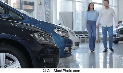 Couple walks along the row of cars at the dealership - Young...