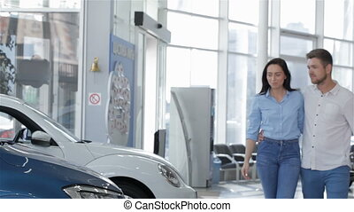Couple chooses the car at the dealership - Attractive young...