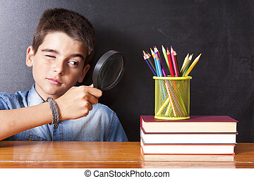 boy with magnifier looking schoolbooks