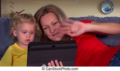 mother with daughter blow kiss to father on tablet video conversation