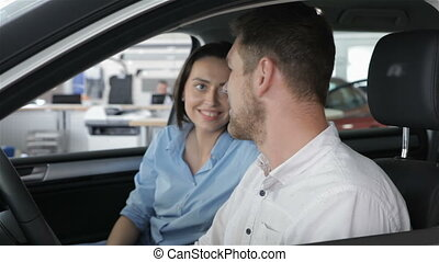 Couple talks inside the car at the dealership - Young couple...