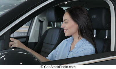 Woman touching the steering wheel in the car - Attractive...